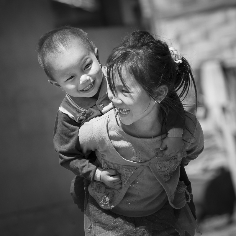 Dans un village Akha, à la frontière chinoise, une fillette porte son petit frère